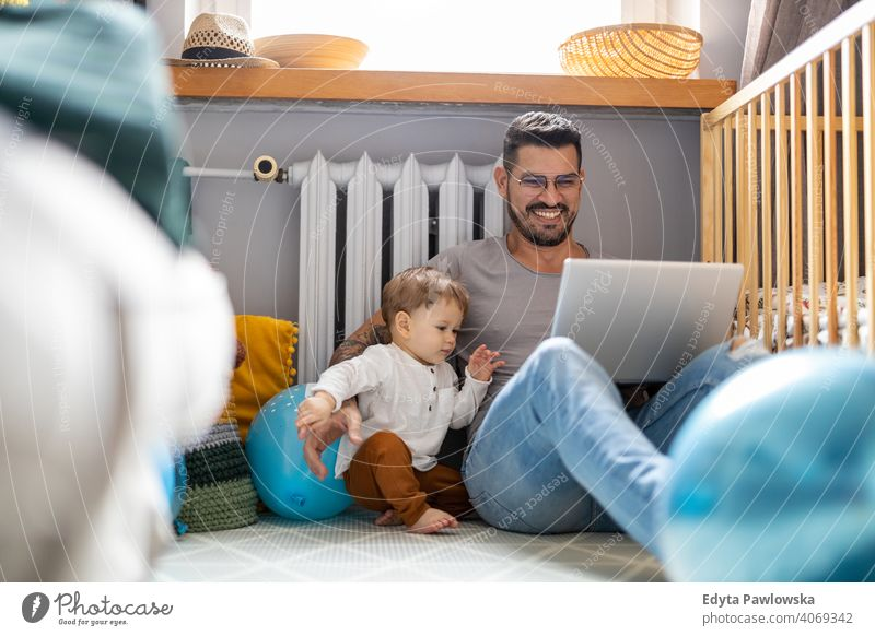 Father trying to work from home single parent single dad fathers day fatherhood stay at home dad paternity leave modern manhood family son child house girl