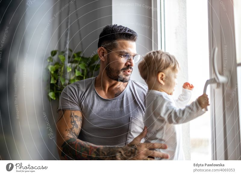 Man with his little son looking through the window at home single parent single dad fathers day fatherhood stay at home dad paternity leave modern manhood
