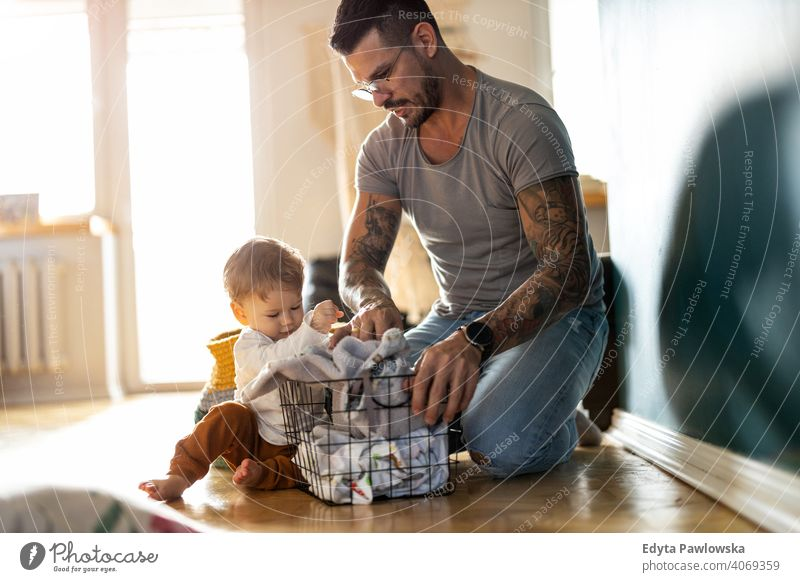 Father and son doing laundry together single parent single dad fathers day fatherhood stay at home dad paternity leave modern manhood family child house girl