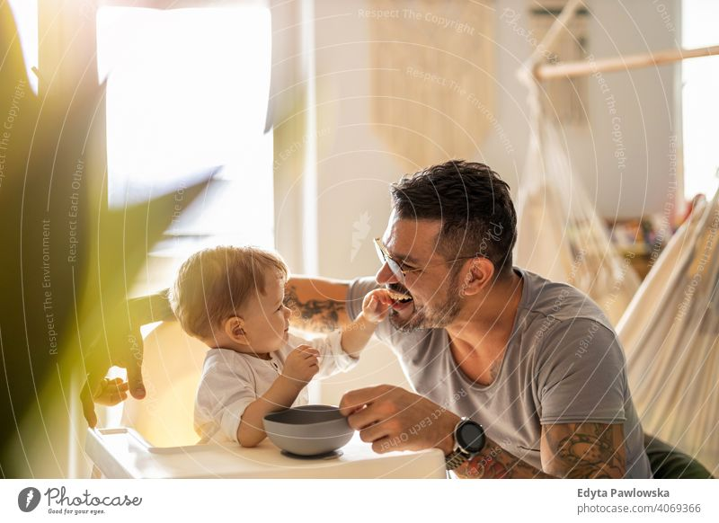 Single dad feeding his baby who is sat in a high chair single parent single dad fathers day fatherhood stay at home dad paternity leave modern manhood family