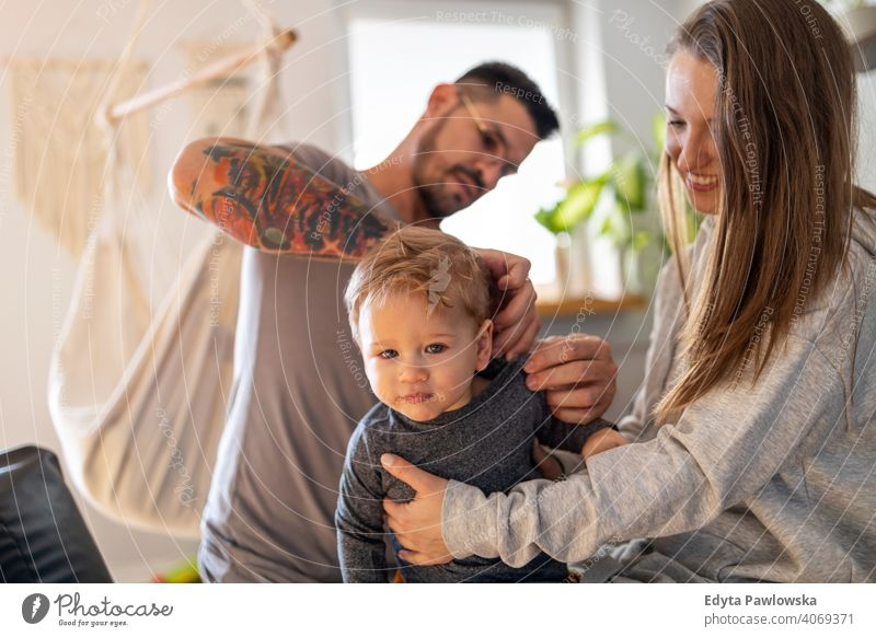 Young couple dressing their little son at home family father child house girl adorable toddler parenting room daughter apartment handsome playing playful infant