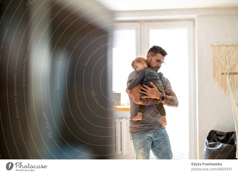 Dad putting to sleep baby boy in his arms at home single parent single dad fathers day fatherhood stay at home dad paternity leave modern manhood family son