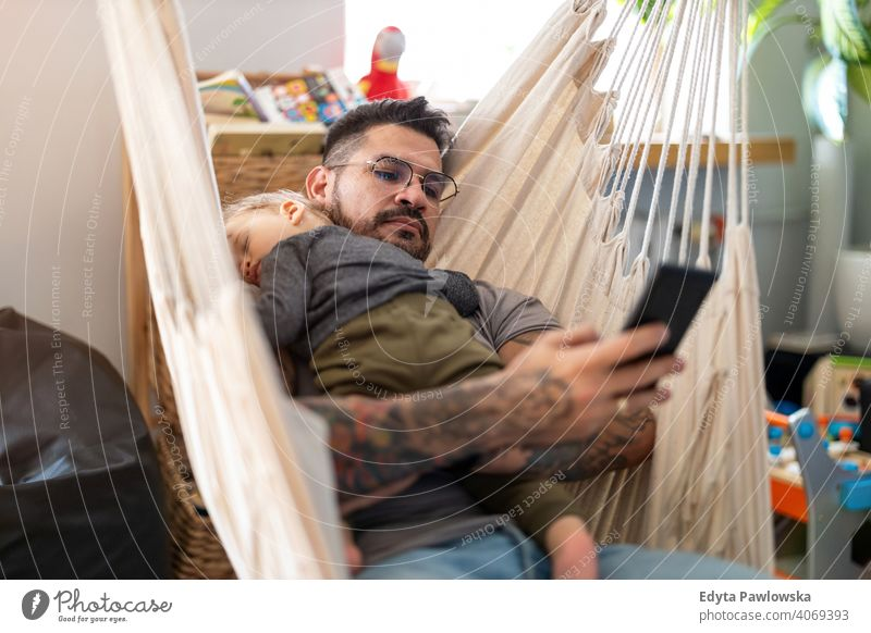 Man checking his phone while his little baby son is sleeping single parent single dad fathers day fatherhood stay at home dad paternity leave modern manhood