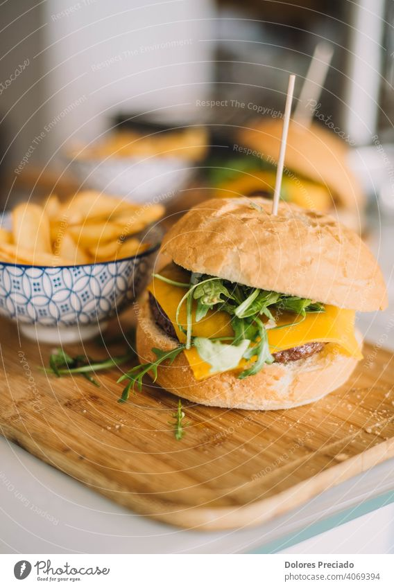 gourmet burger with cheddar cheese, tomato, mayonnaise, arugula and served with deluxe fries Cheeseburger Fast food homemade tabletop Bacon Glittering