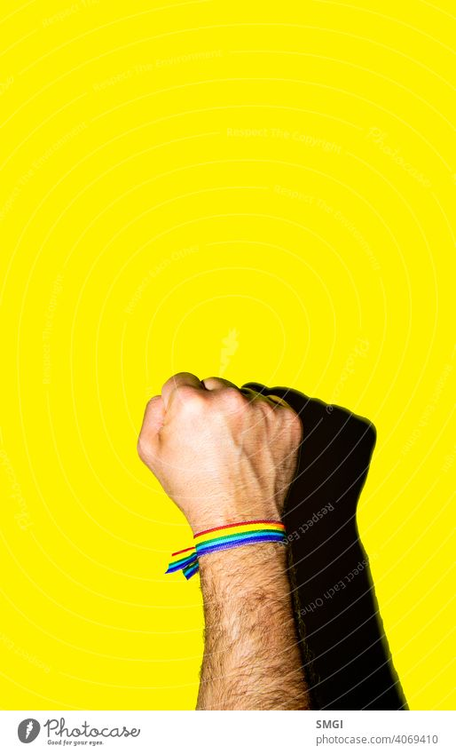 A man's fist held high with a bracelet in the colors of the gay flag. celebrate celebration colorful colour community discrimination diversity equal equality