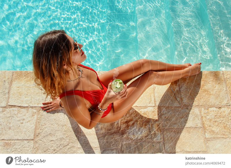 Young woman in red swimsuit with tropical cocktail mojito pool water one-piece Summer top view caucasian Fashion alone Happy smile Garden Emotion Outdoor Exotic