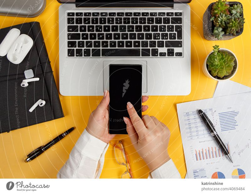 Business woman hands using smart phone top view use smartphone documents cell phonereports yellow laptop desk office coffee Caucasian faceless Charts Graphs