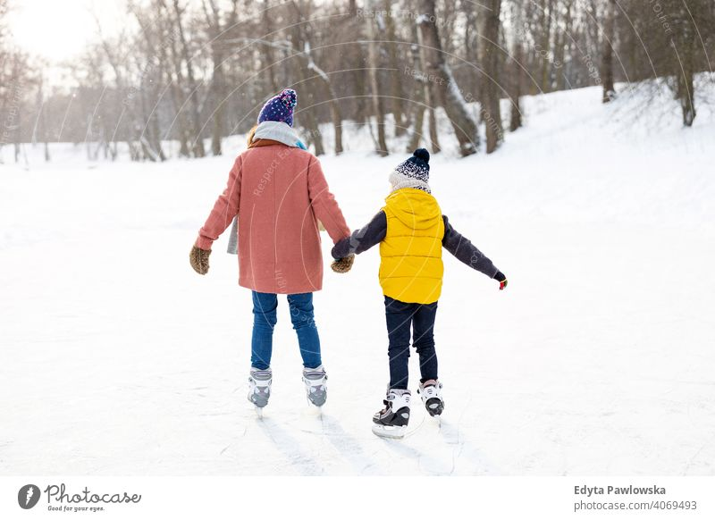Mother and son ice-skating on frozen pond mother daughter season together cheerful fun kid people park holiday forest childhood woman girl nature joy snow cold