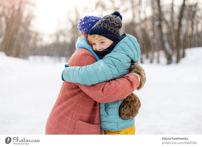 Mother and son hugging outdoors in snow mother daughter season together frozen cheerful fun kid people park holiday forest childhood woman girl nature joy cold