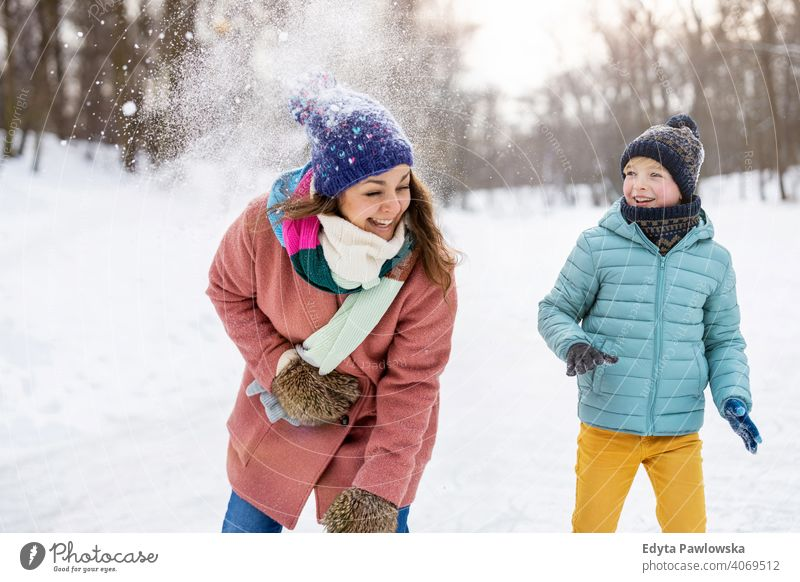 Mother and kid having snowball fight in winter park mother son daughter season together frozen cheerful fun people holiday forest childhood woman girl nature
