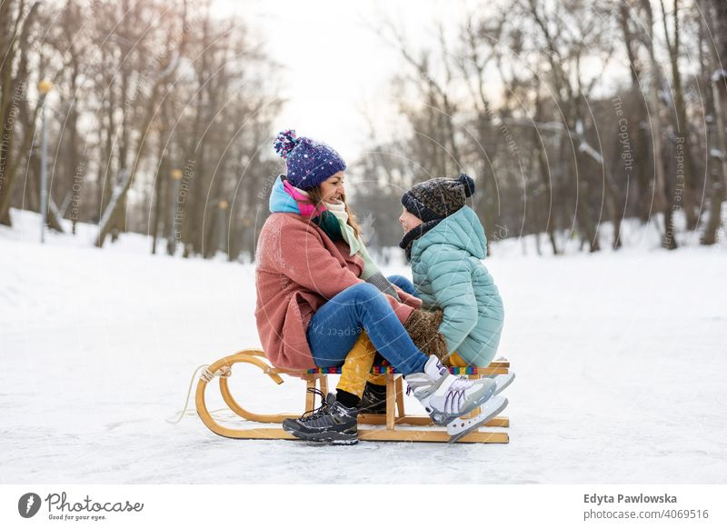 Mother and son having a great winter day outdoors playing in the snow mother daughter season together frozen cheerful fun kid people park holiday forest