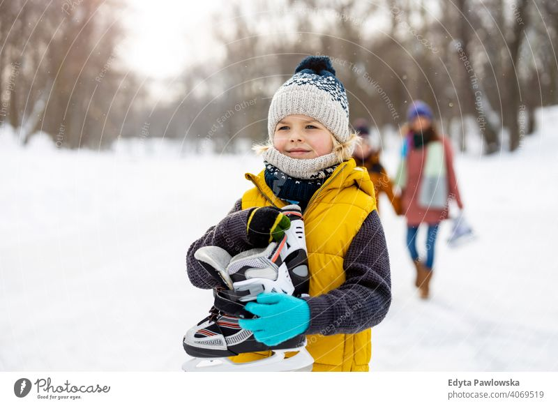 Little boy going ice skating with his family mother son daughter season together frozen cheerful fun kid people park holiday forest childhood woman girl nature