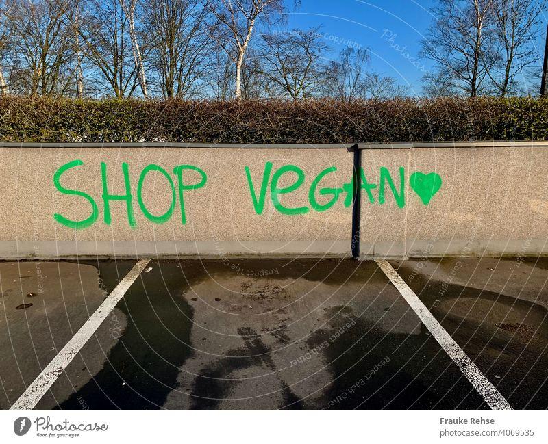 SHOP VEGAN - written in green letters on a wall in a parking lot vegan Vegan diet veganism vegan shopping Verdant purchasing Parking lot invitation Heart Green