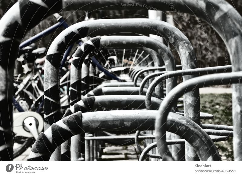 Black and white photograph Central view through a bicycle stand Wheel Bicycle rack Parking White black-white Metal Spokes Cycling Detail Street Exterior shot