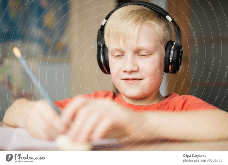 Boy in headphones writing and smiling. boy kid child indoor cute smile homework fun write caucasian blond hand pencil hair face person childhood music listening