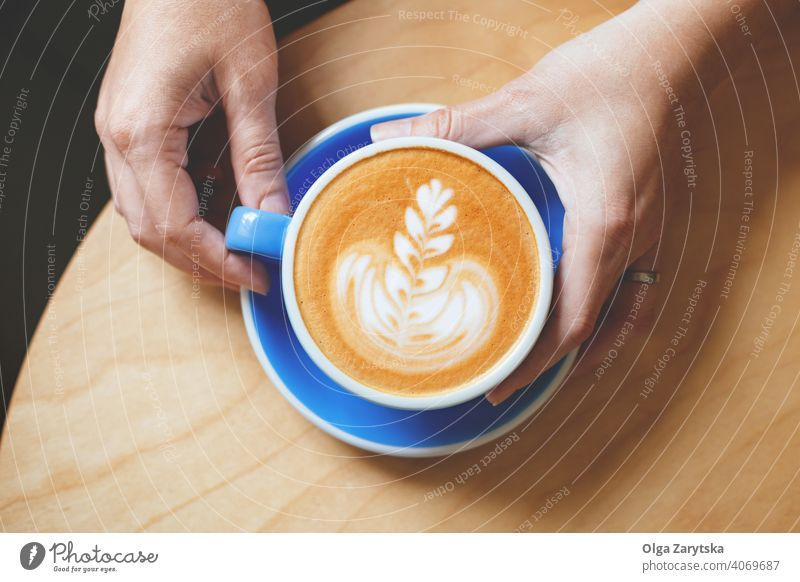 Woman's hand holding a coffee with latte art. woman cappuccino cup mug background person vintage white cafe drink espresso hot top beverage breakfast caffeine