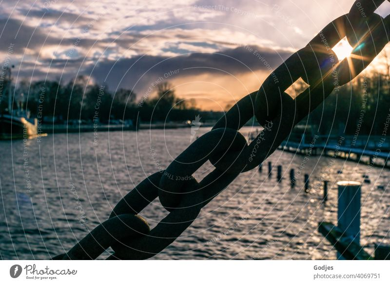 Sun shines through link of massive steel chain against cloudy sky of dusk over river Chain Chain links Sunbeam Clouds Dusk River boat ship Water Sky Tourism