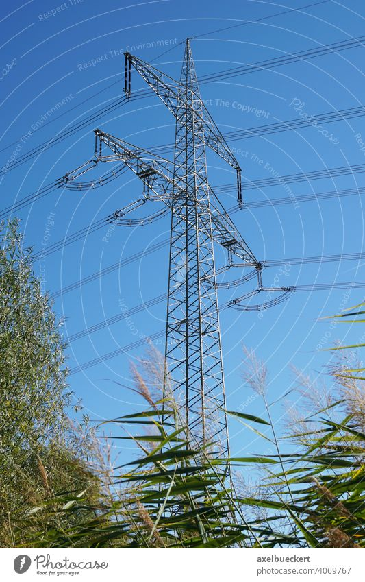 high-voltage transmission tower or pole or electricity pylon power line energy overhead utility cable high-tension conductor nature sky industry technology