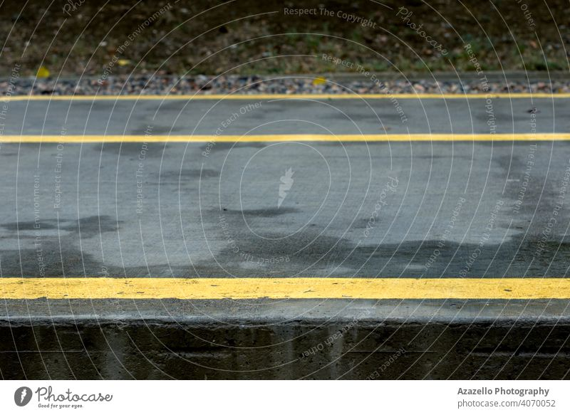 Yellow lines and arrows on a wet concrete path in the park. asphalt background black city dark day direction drive grey guidance highway indicate journey lane