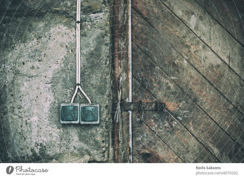old sockets on concrete wall and wooden vintage door Abstract apartment architecture background business cobweb concept construction decay dirty electric