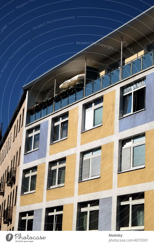 Restored two-tone façade in beige and blue with covered balcony in summer sunshine in the city centre of Frankfurt am Main in the German state of Hesse