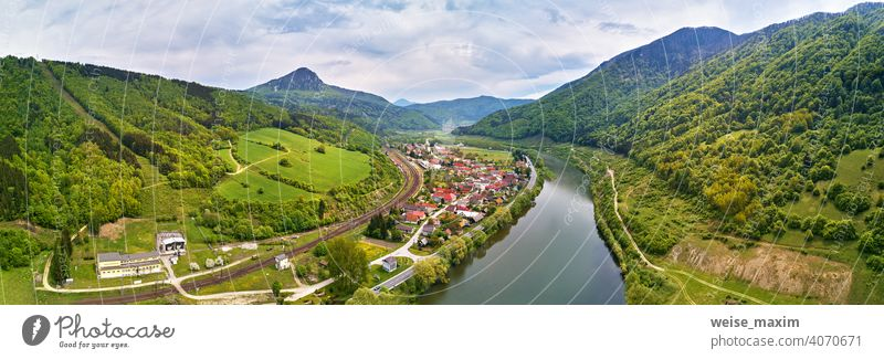Village, river and road in mountain valley. Green mountain meadows and hills. Kraľoviansky meander on river Bar. Spring panorama Tatra spring landscape rain