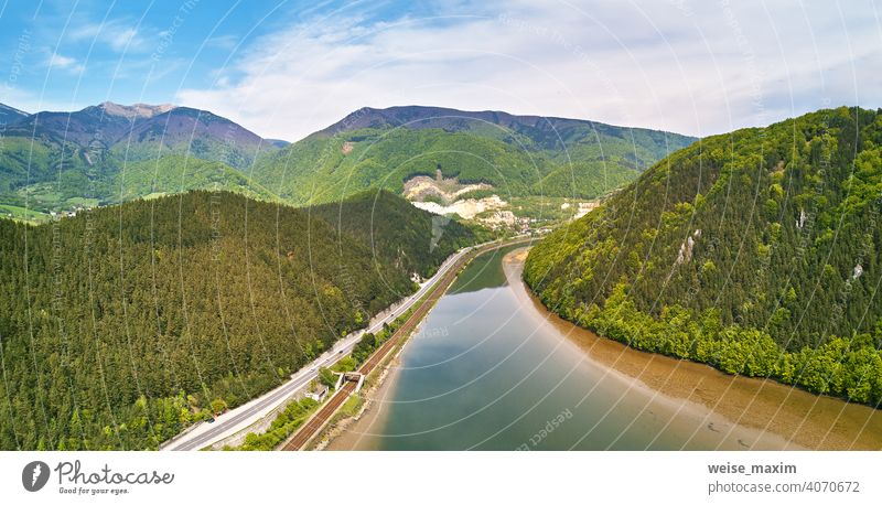 Village, river and road in mountain valley. Green mountain meadows and hills Tatra spring panorama landscape rain green Slovakia forest summer village railroad