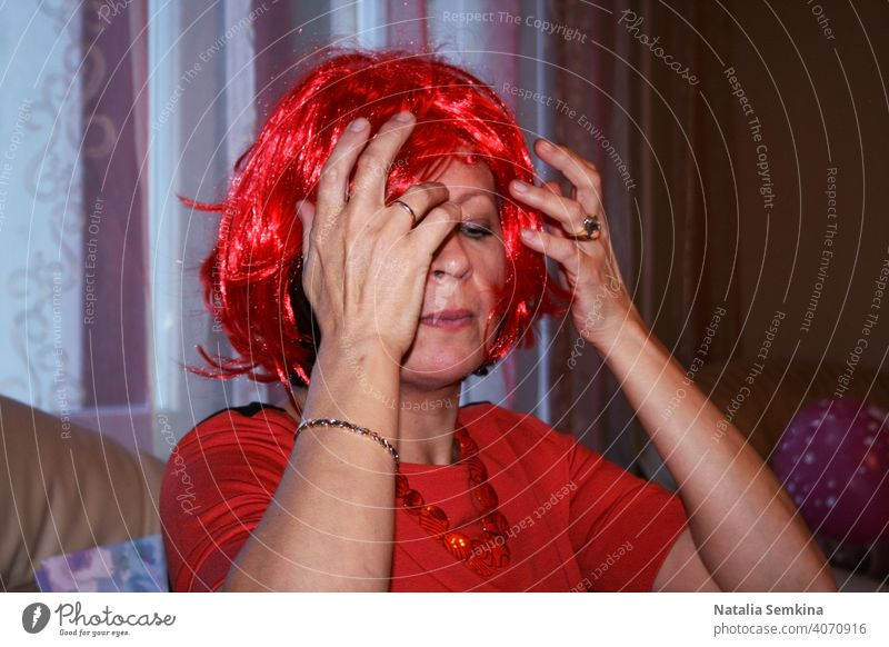 A woman is sitting at sofa and adjusting fiery red wig on her head at birthday party. Head and shoulders portrait. Party at home. female face head and shoulders