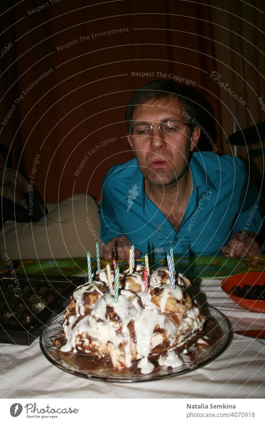 Man in blue shirt blowing out burning candles on  handmade festive cake in dark room. Birthday celebration at home. Party at home. Waist portrait. Vertical orientation.