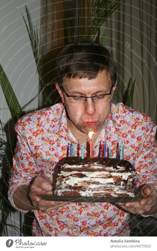 Man in floral shirt holding handmade festive cake in her hands and blowing out burning candles in dark room. Birthday celebration at home. Party at home. Waist portrait. Vertical orientation.