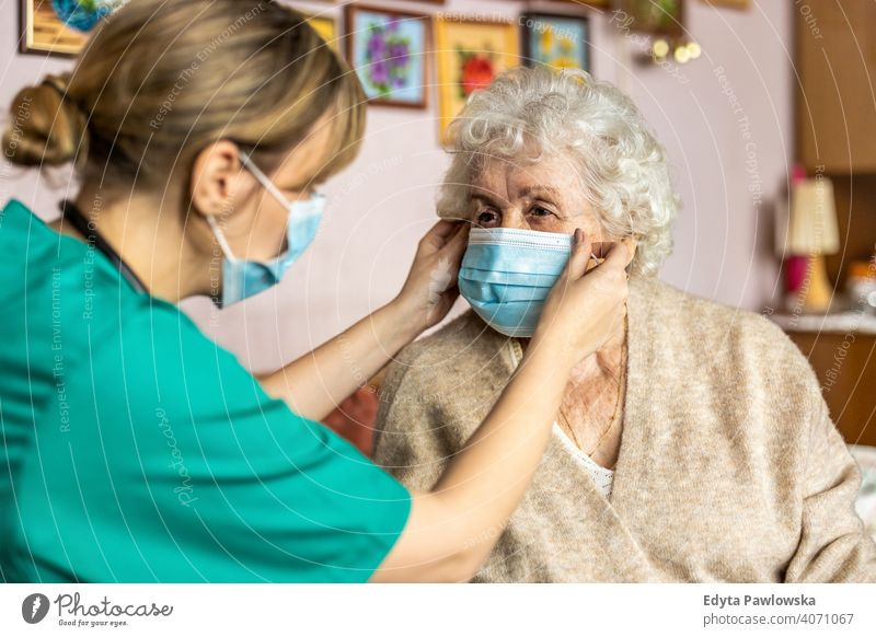 Female nurse helping a senior woman to put on protective face mask during home visit coronavirus real people covid elderly candid genuine mature female