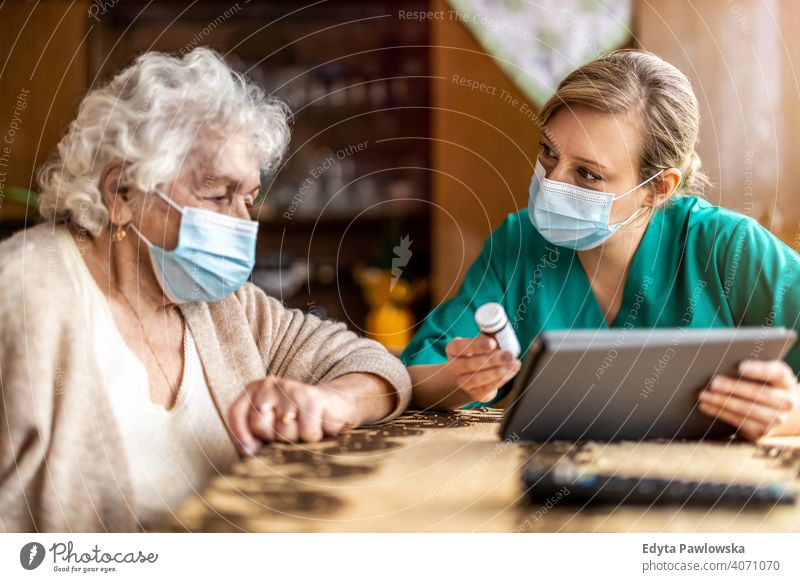 Home caregiver helping senior woman with medication coronavirus face mask real people covid nurse elderly visit candid mature female Caucasian home house old