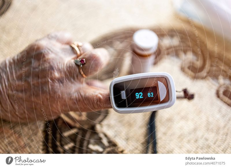 Oximeter for checking oxygen saturation in blood on senior woman's hand real people candid genuine mature female Caucasian elderly home house old aging