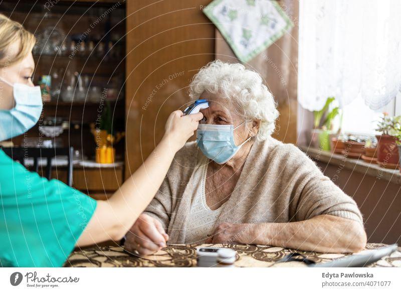 Female nurse checking temperature to senior woman during home visit coronavirus face mask real people covid elderly candid genuine mature female Caucasian house