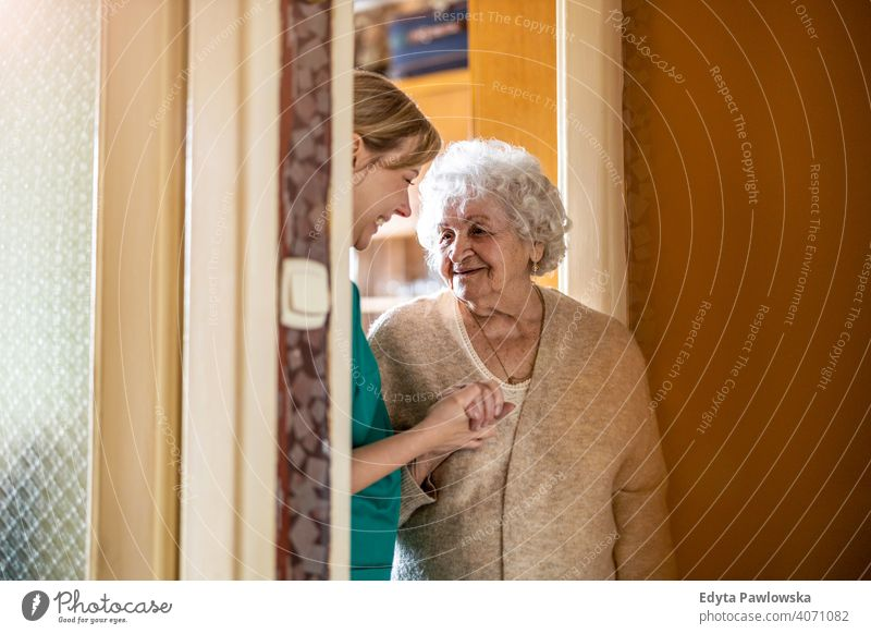 Friendly nurse supporting an elderly lady real people candid genuine woman senior mature female Caucasian home house old aging domestic life grandmother