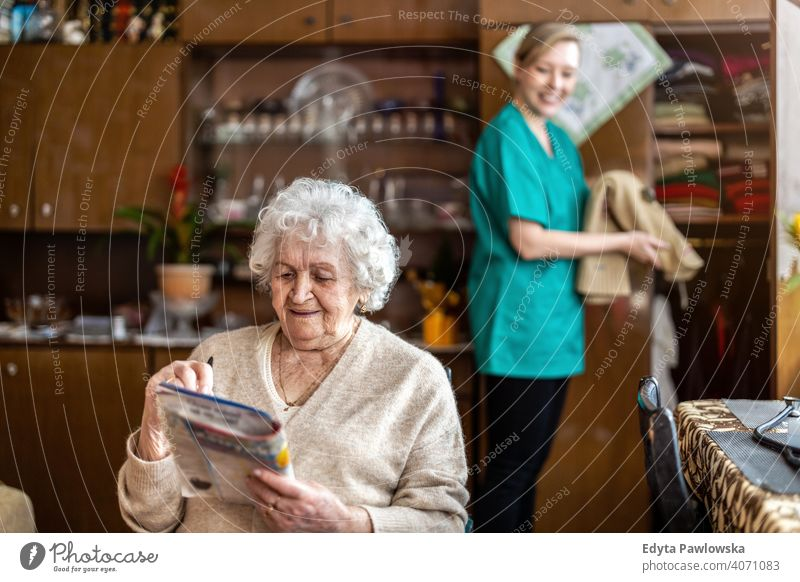 Female nurse taking care of a senior woman at home real people candid genuine mature female Caucasian elderly house old aging domestic life grandmother