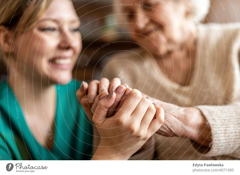 Cropped shot of a senior woman holding hands with a nurse consoling wrinkled real people candid genuine mature female Caucasian elderly aging grandmother