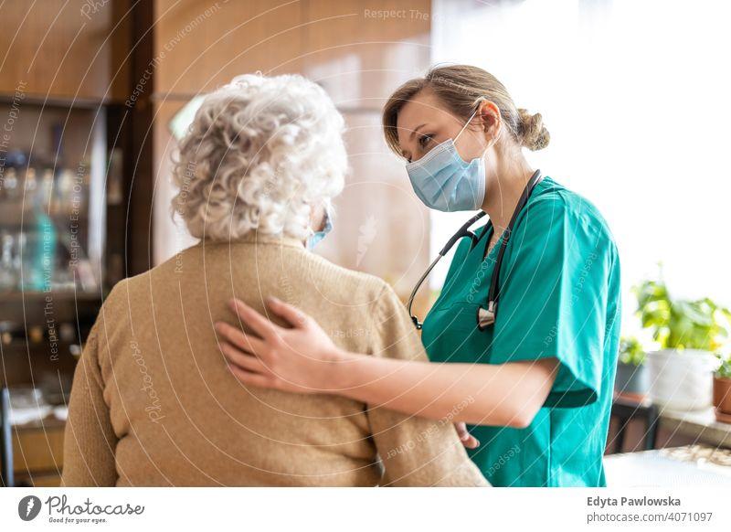 Senior woman visited by home care specialist during lockdown coronavirus face mask real people covid senior nurse elderly candid genuine mature female Caucasian