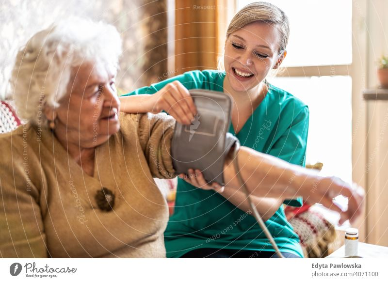 Female caretaker measuring senior woman's blood pressure at home real people candid genuine mature female Caucasian elderly house old aging domestic life