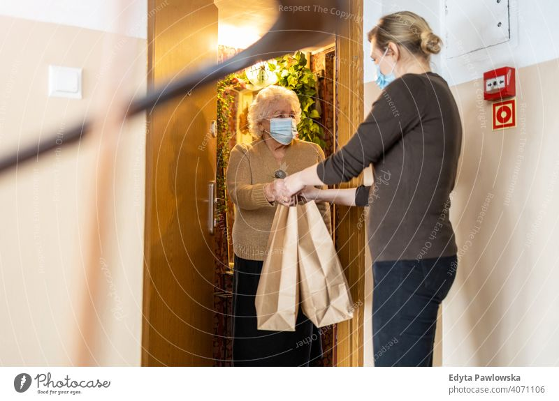 Female volunteer delivering bags with shopping to elderly woman during coronavirus pandemic delivery grocery food lockdown quarantine door face mask