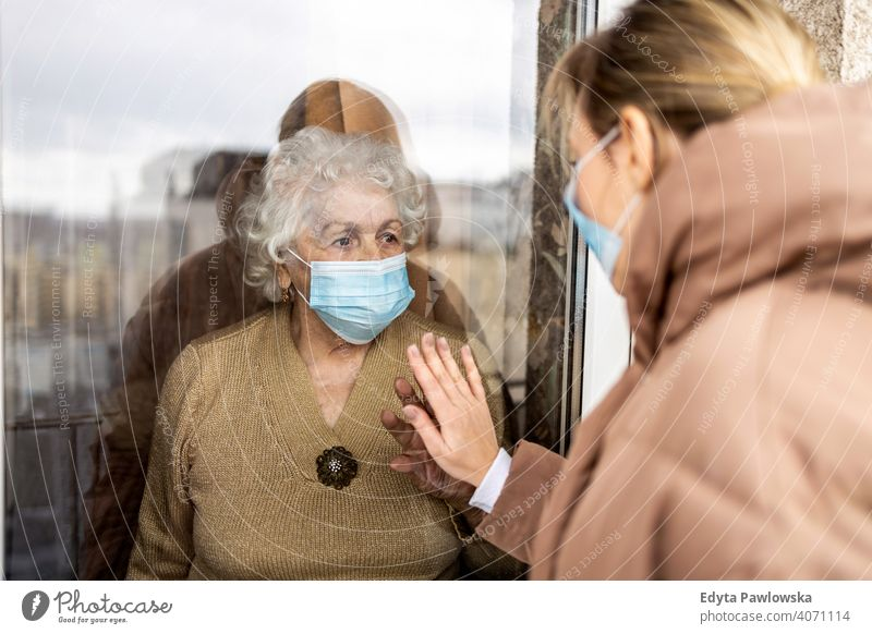 Woman visiting her grandmother in isolation during a coronavirus pandemic window covid lockdown looking quarantine looking through window social distancing