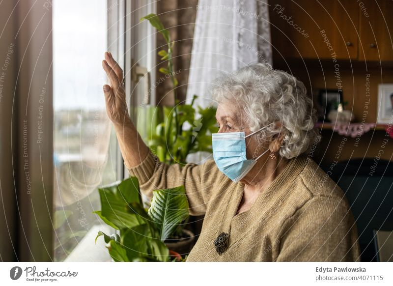 Senior woman with face mask looking out of window at home covid lockdown coronavirus quarantine looking through window social distancing glass vulnerable