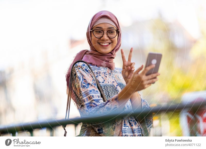 Young woman wearing a hijab taking a selfie headscarf muslim islam arabic summer girl people young adult female lifestyle active outdoors millennial outside