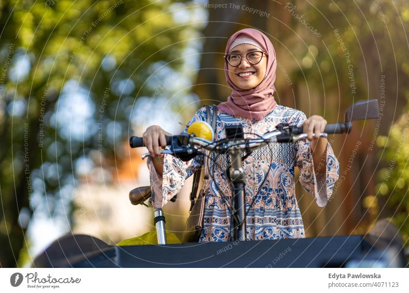 Confident Muslim woman using cargo bike in urban area hijab headscarf muslim islam arabic summer girl people young adult female lifestyle active outdoors