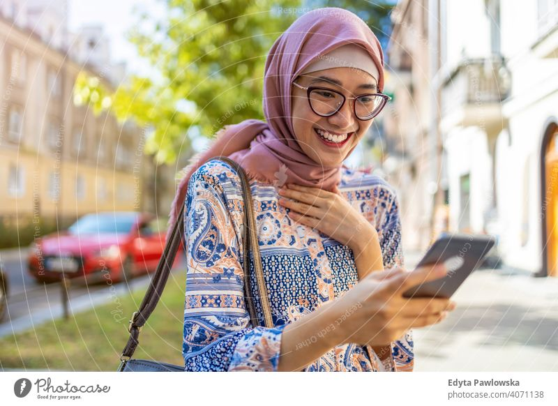 Smiling young muslim woman using mobile phone outdoors hijab headscarf islam arabic summer girl people young adult female lifestyle active millennial outside