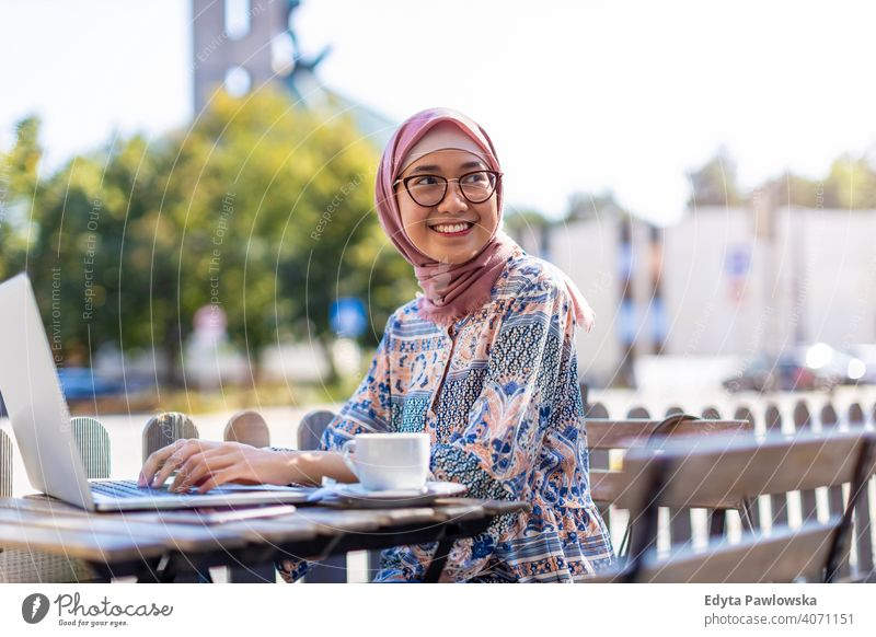 Young Muslim woman using a laptop in outdoor cafe hijab headscarf muslim islam arabic summer girl people young adult female lifestyle active outdoors millennial