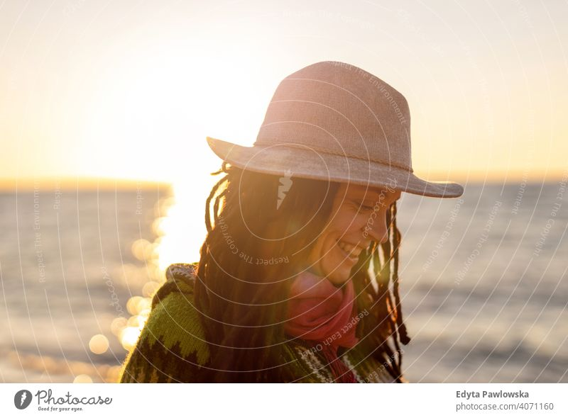 Young woman in a hat on the beach at sunset travel tourist tourism vacation backpacker beautiful attractive young adult people outdoors casual Greece happy joy