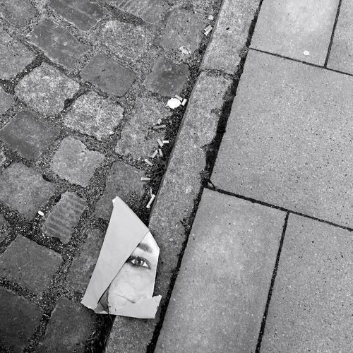 careless Image portrait Poster EXCERPT section Street paving stone Cigarette Butt Woman Face Eyes Looking Paper off