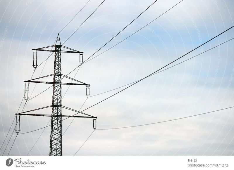 Power pole with high voltage lines against cloudy sky Electricity pylon Power lines Energy High voltage power line Energy industry Technology Transmission lines