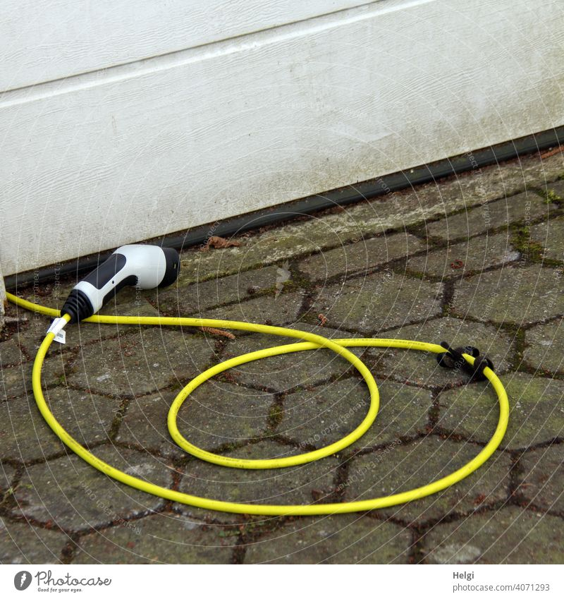 yellow charging cable with plug lies in front of a garage and waits for the electric car Cable charger cable Connector power supply Electricity Technology